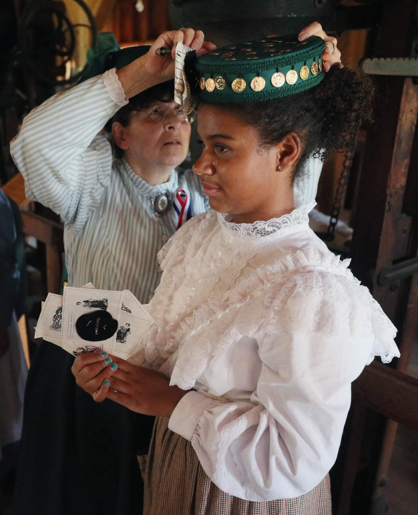 Millinery Anderson helps secure Crista Manning's hat as the two prepare to march in a 1897 Fourth of July Celebration in Railroad Town at Stuhr Museum.