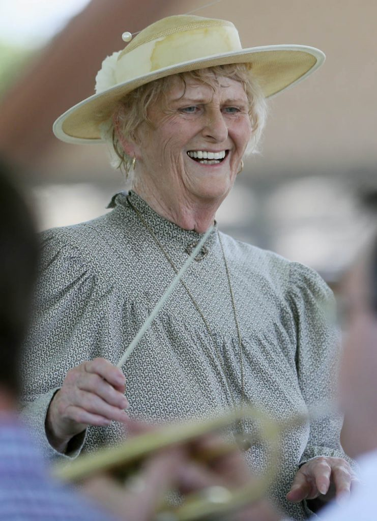 Judy Miller smiles while conducting the Railroad Town Silver Cornet Band plays during a 1897 Fourth of July Celebration in Railroad Town at Stuhr Museum.