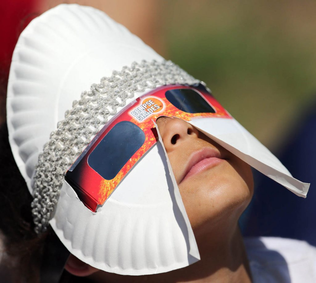Phoenix Grim of Omaha wears a makeshift mask including a paper plate and head band with her solar glasses at Liberty Range in Dannebrog, Neb. Monday.