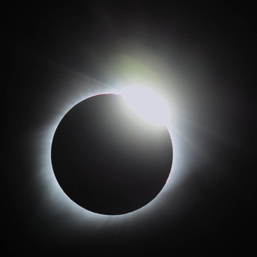 A diamond ring appears on the top right as pearls of sunlight shining through valleys and mountains of the moon called Bailey's beads shimmer during totality of a solar eclipse spanning across 10 states as viewed at Liberty Range in Dannebrog, Neb.
