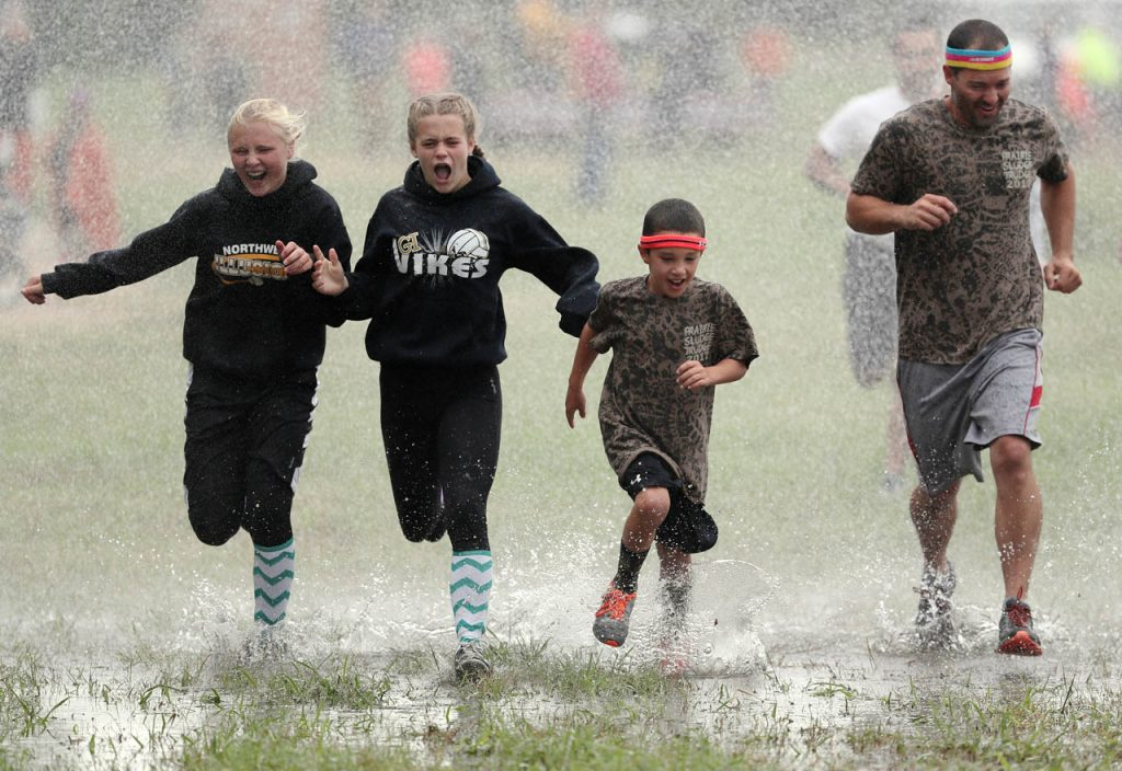 Runners make a trek across an open field running through water being sprayed by a Rural Grand Island Fire Dept. firehose during the Prairie Sludge Trudge at Stuhr Museum.