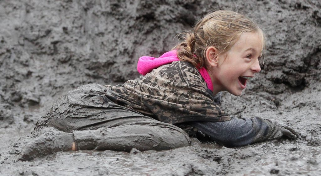 Aubrey Vontz reacts after sliding down a mud mountain during Prairie Sludge Trudge Saturday at the Stuhr Museum.