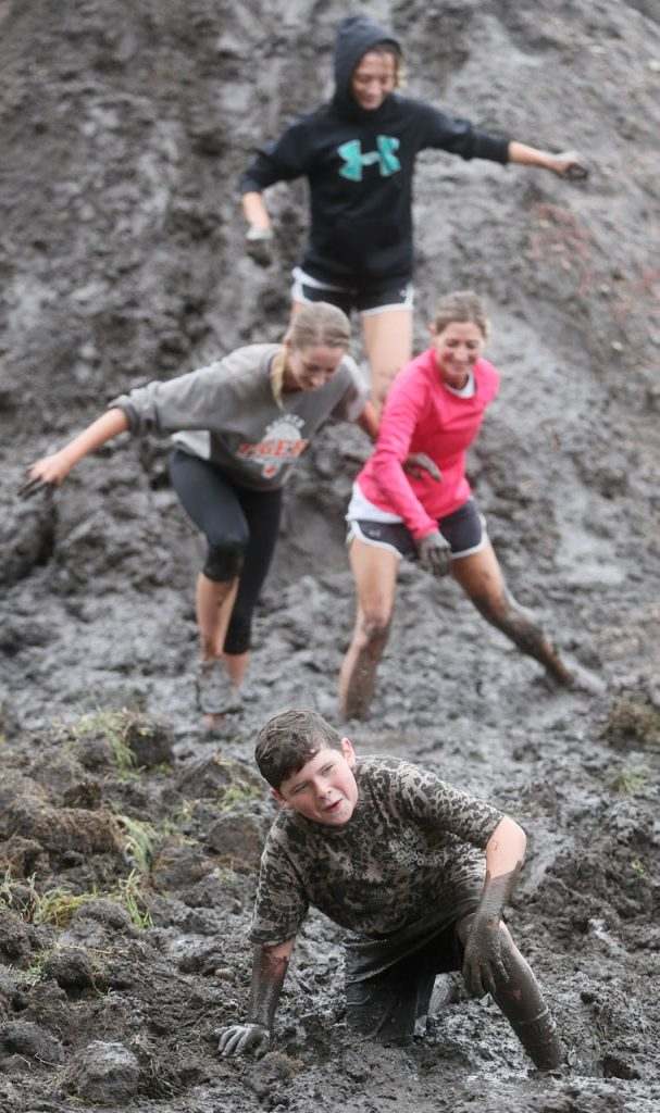 Participants come down a 10' high mountain of mud one by one during the Prairie Sludge Trudge at Stuhr Museum.