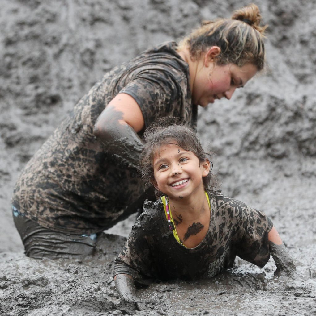 Anahi Garcia smiles after sliding down a mud mountain with her mother Anna during Prairie Sludge Trudge Saturday at the Stuhr Museum.