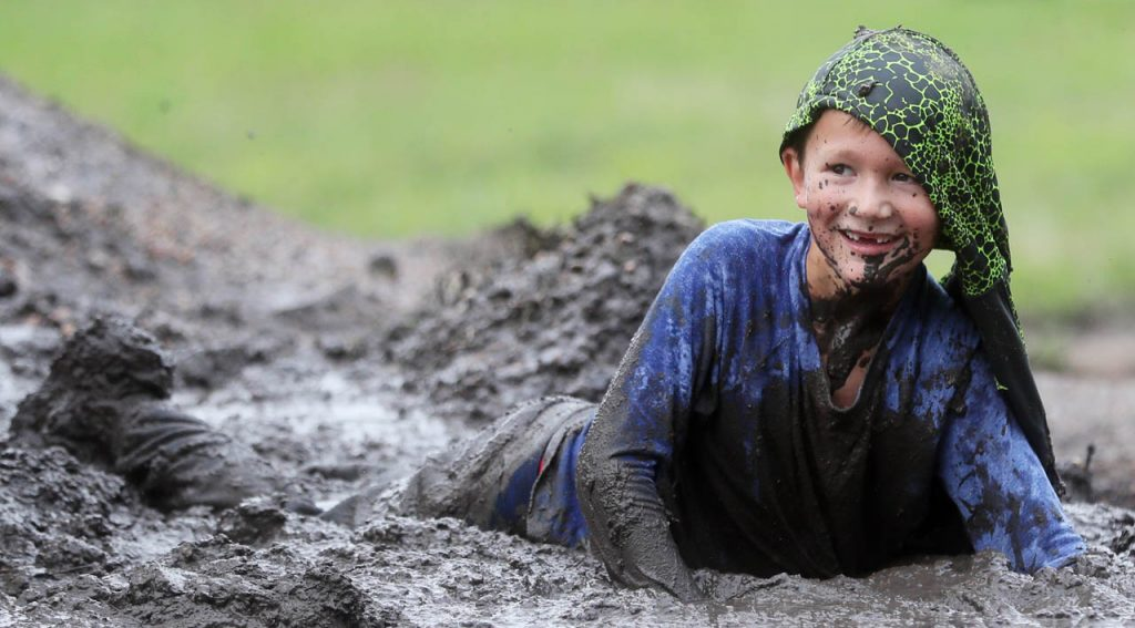 A young boy is covered in mud during the Prairie Sludge Trudge at Stuhr Museum.