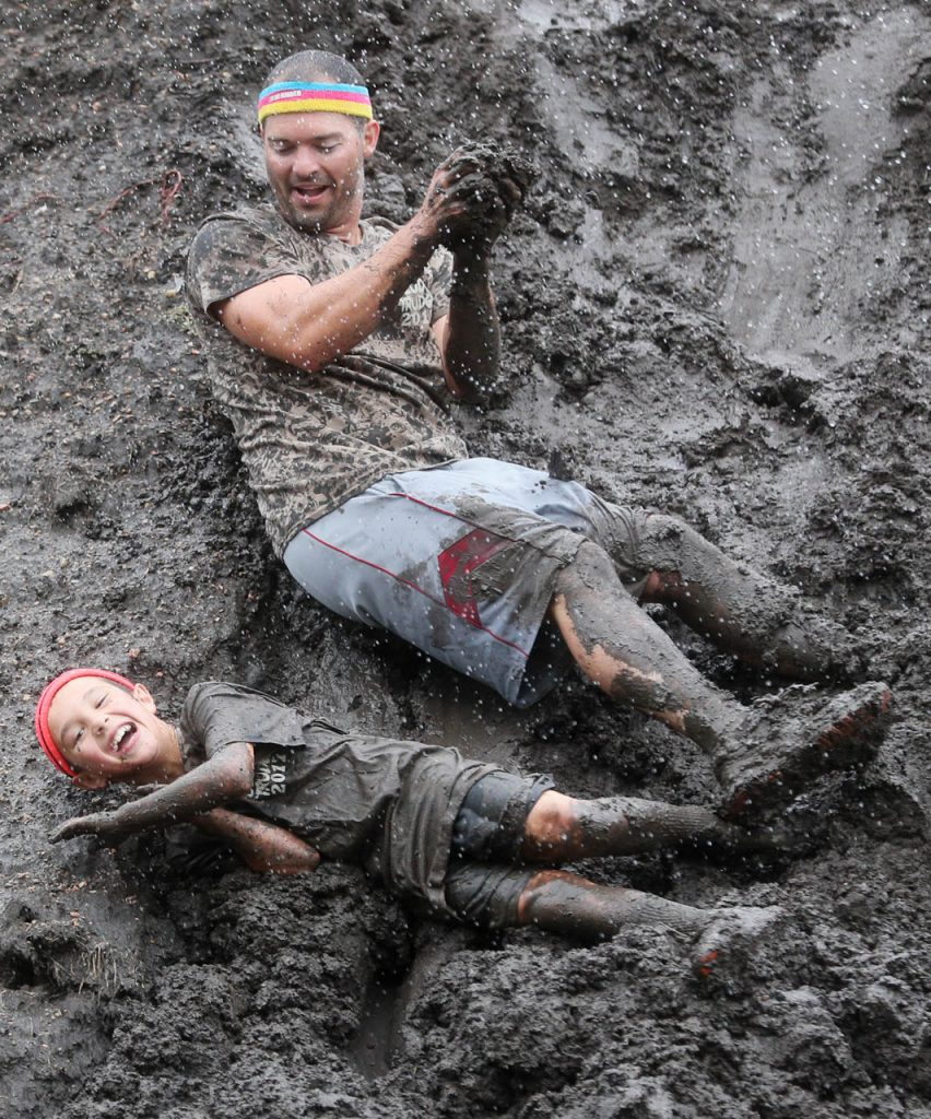 A father and son roll down a 10' high mountain of mud during the Prairie Sludge Trudge at Stuhr Museum.