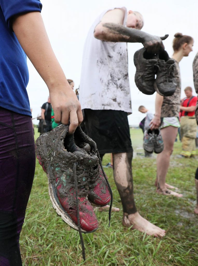 Rachel Cloran, left, holds her muddy shoes while waiting in line to be sprayed down concluding Prairie Sludge Trudge Saturday at the Stuhr Museum.