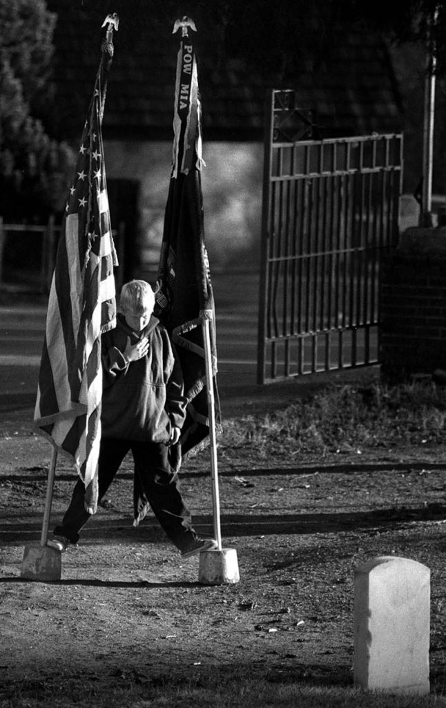 A youngster braces his feet between two flag posts while placing his hand over his heart during the playing of the National Anthem at a Veteran's Day service at Littleton cemetery.