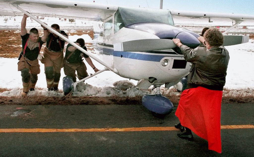 An airline manager assists firefighters in removing a Cessna from a snowdrift where it crash landed shy of Centennial Airport due to mechanical failure.