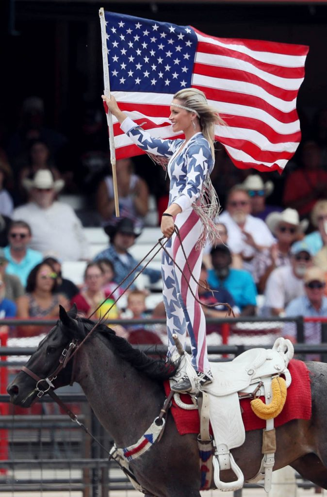 A member of The Riata Ranch Cowboy Girls stands on top of her horse while holding an American flag on the arena track during a Cheyenne Frontier Days rodeo. (Photo by Andrew Carpenean)