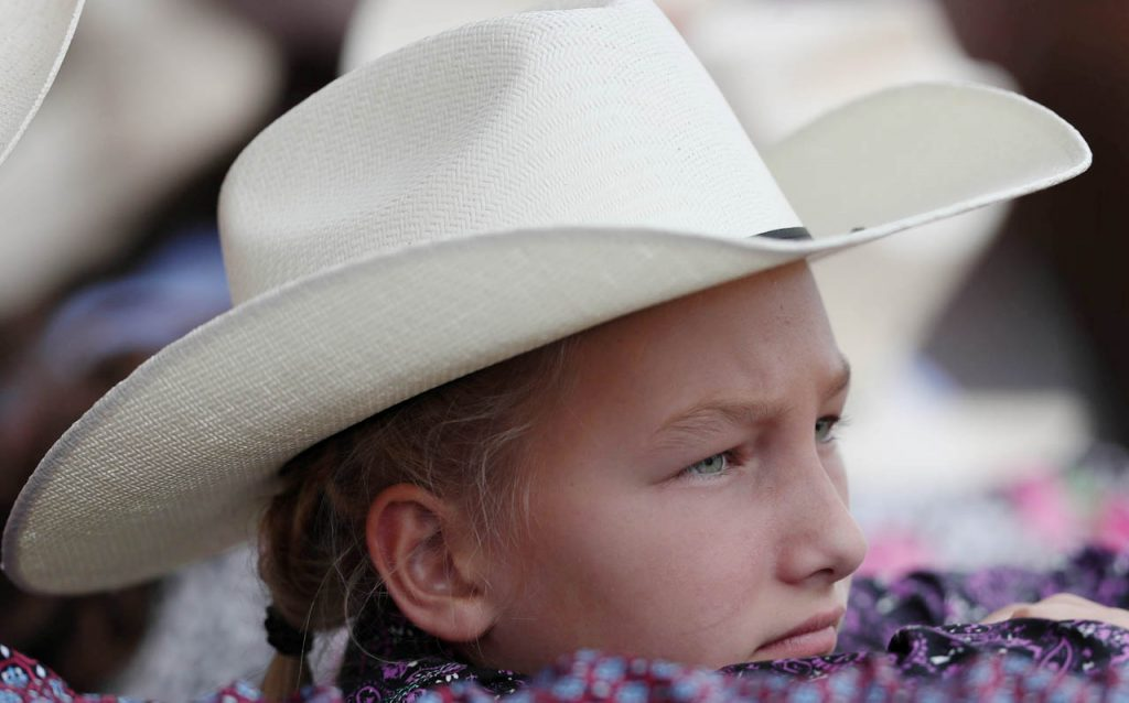 Trona Bates of Cheyenne, Wyo. stands in the chutes to watch a Cheyenne Frontier Days rodeo.