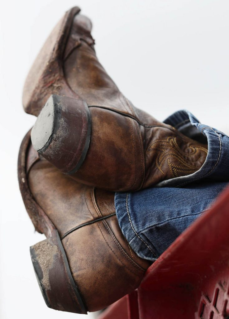 A cowgirl kicks her heels up on a railing while watching a Cheyenne Frontier Days rodeo.