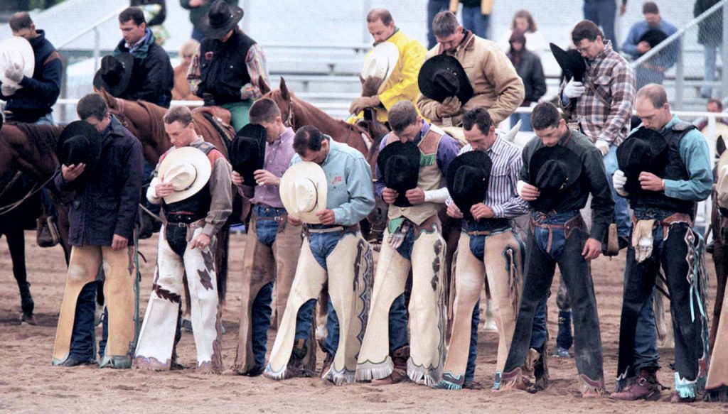 Rodeo cowboys reflect in a word of prayer prior to the start of a PRCA rodeo at the Douglas County Fairgrounds in Castle Rock, Colo.