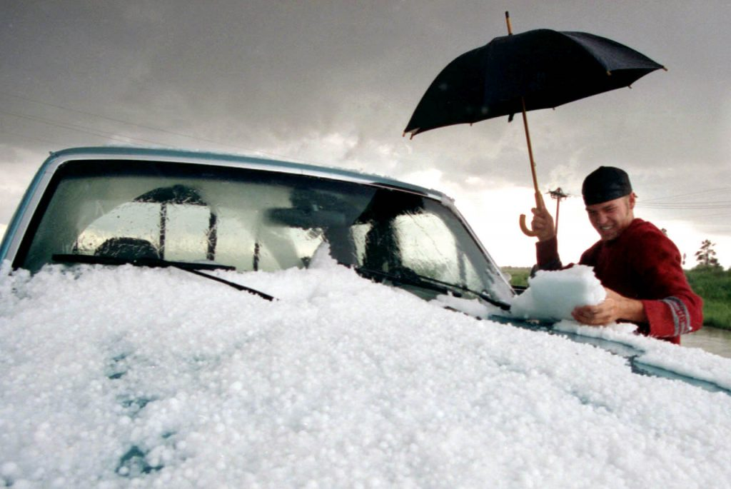 A motorist removes clumps of hail stuck together from his pickup truck windshield after a heavy hail from a passing severe thunderstorm in Parker, Colo.