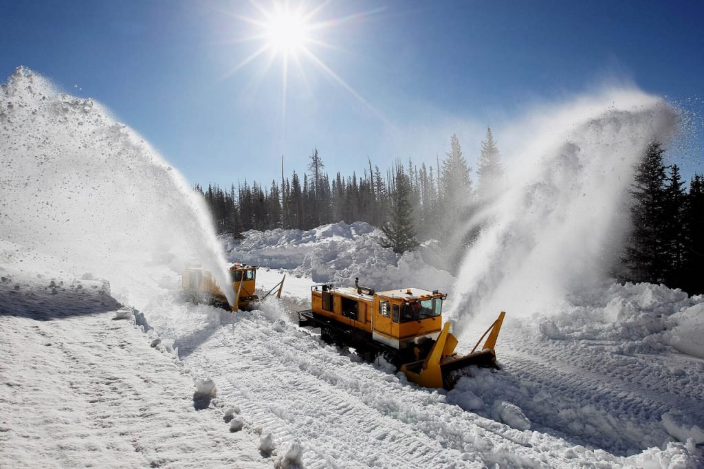 Snow cascades into treetops from commercial rotary blowers as WYDOT crews break through a record snowfall to open the alpine roadway between Centennial and Saratoga along Snowy Range Pass.