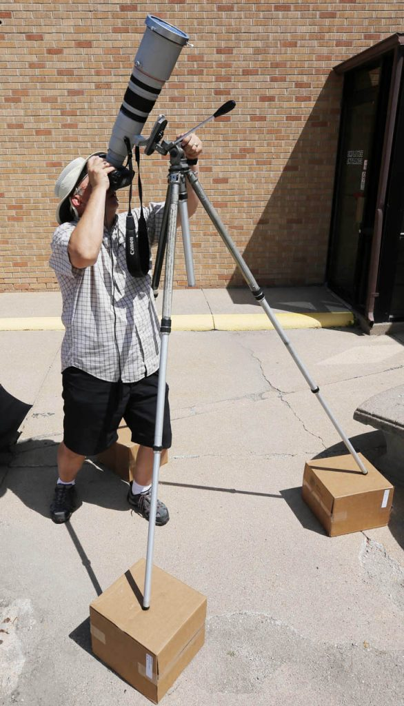 Barrett Stinson, photo editor at The Grand Island Independent, uses three boxes to prop up a tripod to photograph a solar eclipse with a Canon EOS 1D Mark II with a 200-400 zoom lens with a built in 1.4x converter and a second 1.4x converter attached. Taking photos approximatley every six minutes throughout the duration of the eclipse outside the newspaper office.