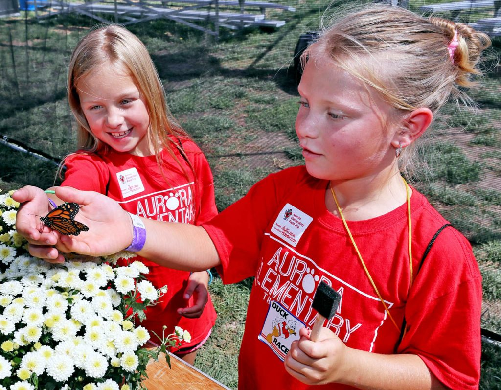 Jersey and Addison Peterson of Aurora Elementary School hold a butterfly together inside Butterfly Encounter of Spring Hill, Fla. during Nebraska's Largest Classroom day at the Nebraska State Fair.