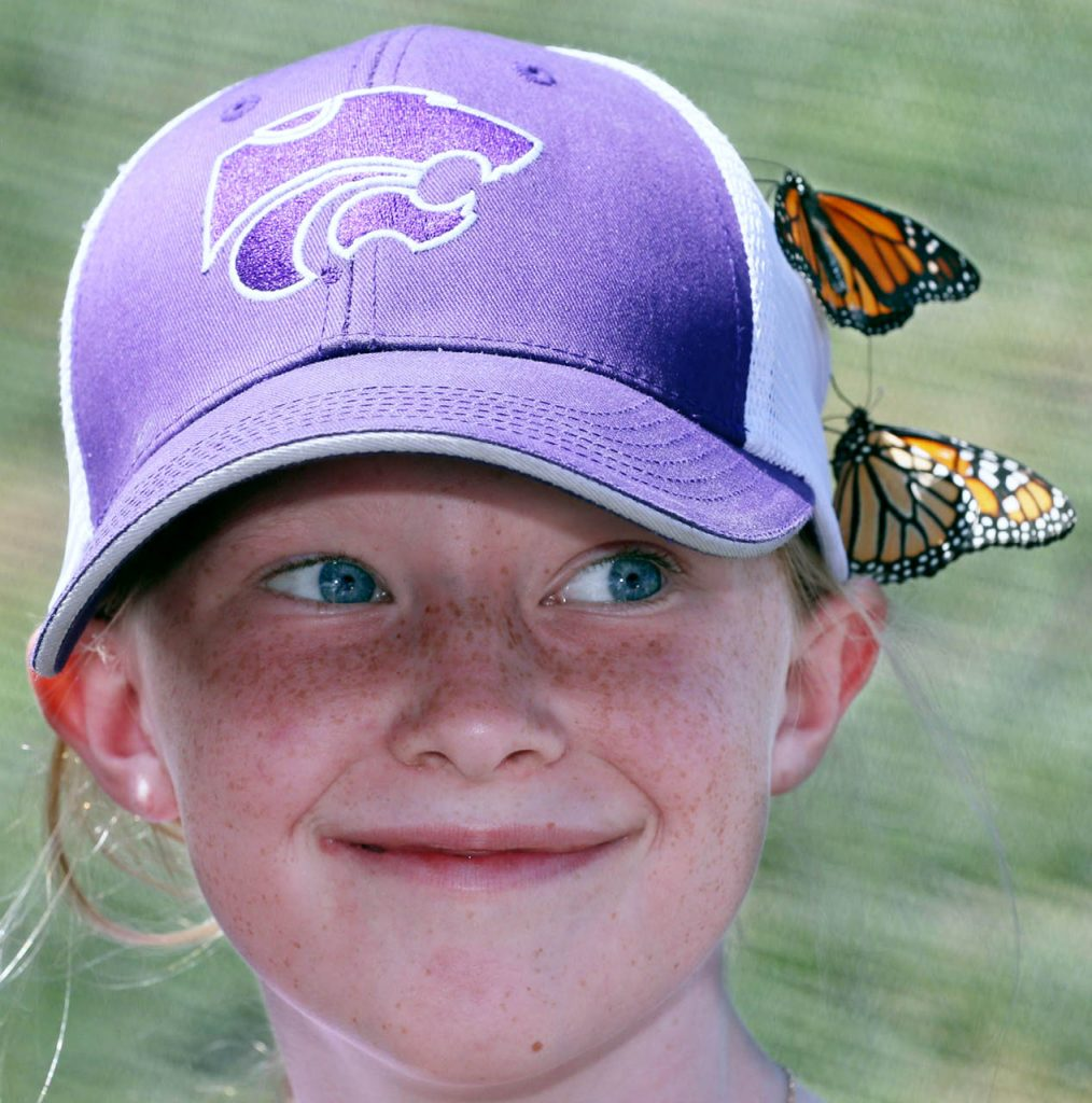 Addy Skaggs a fourth-grader at Axtell Elementary School smiles as two butterflies land of her baseball cap inside Butterfly Encounter of Spring Hill, Fla. during Nebraska's Largest Classroom day at the Nebraska State Fair.