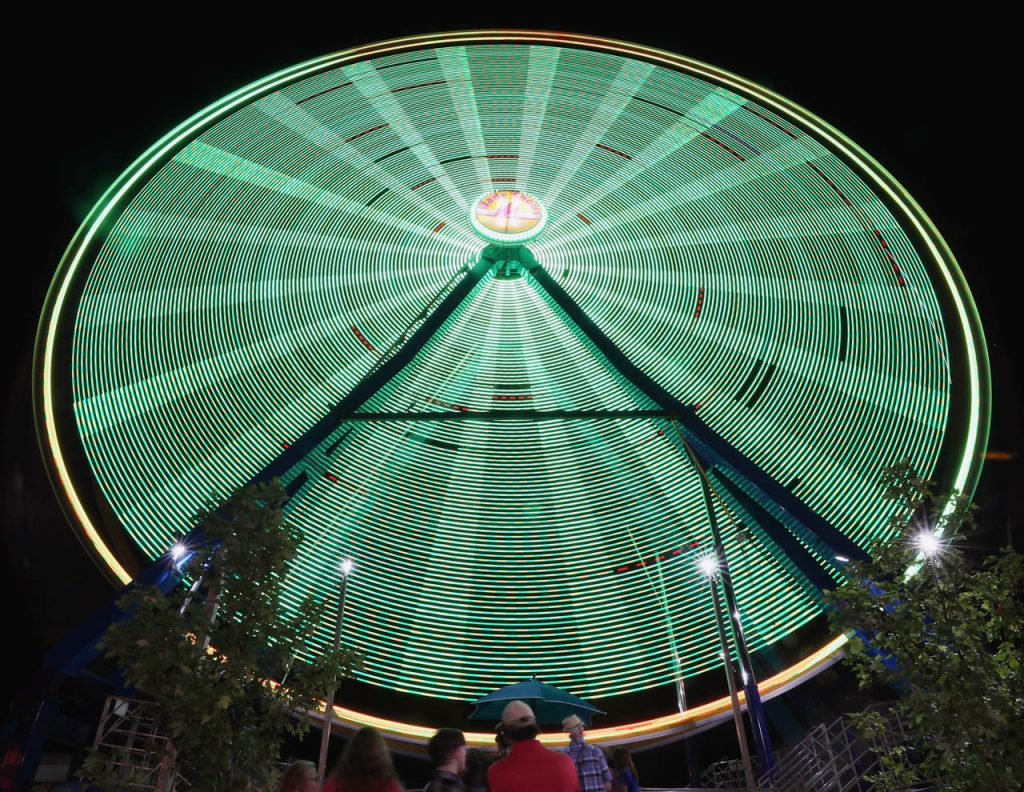 People wait in line to take a ride on the Giant Gondola Wheel on the midway during the Nebraska State Fair.
