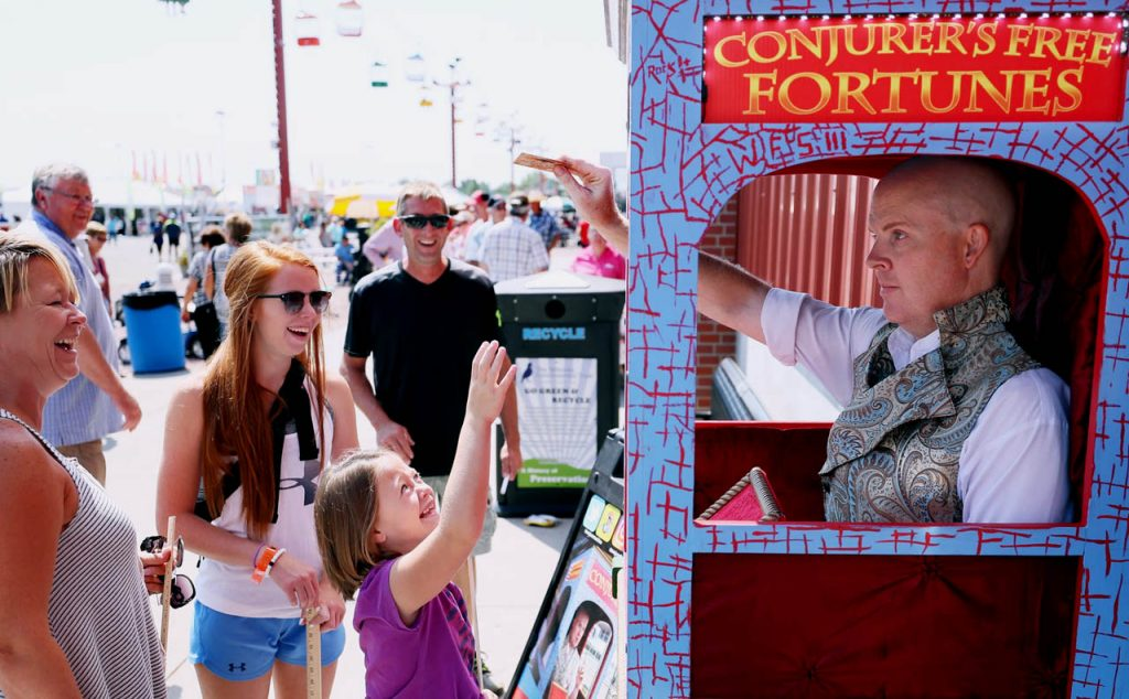 Taylor Penrose of Grand Island jumps to grab her fortune card from Robert Smith of Conjurer Free Fortunes at the Nebraska State Fair. Penrose's fortune was that she would be taller one day.