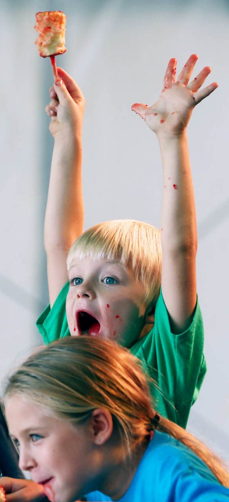 Joseph Liscom of Omaha raises his hands in the air upon winning the Rodney and Lisa's candy apple eating contest at the 2017 Nebraska State Fair.