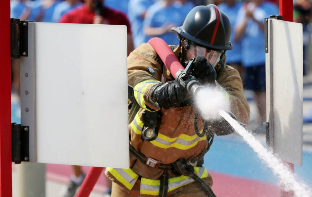 Grand Island firefighter Fred Benzel sprays water at a target with a fire hose over his shoulder while competing in the Scott Firefighter Combat Challenge Saturday at the Nebraska State Fair.