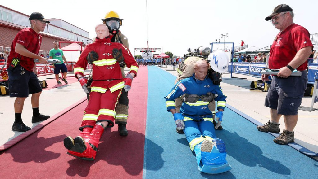 Aaron Armstrong, a Grand Island firefighter, left, lifts a 175-pound rescue mannequin alongside Edgardo Rodriguez, a firefighter with the United States Air Force Academy to drag backwards to the finish line during the Scott Firefighter Combat Challenge Saturday at the Nebraska State Fair.