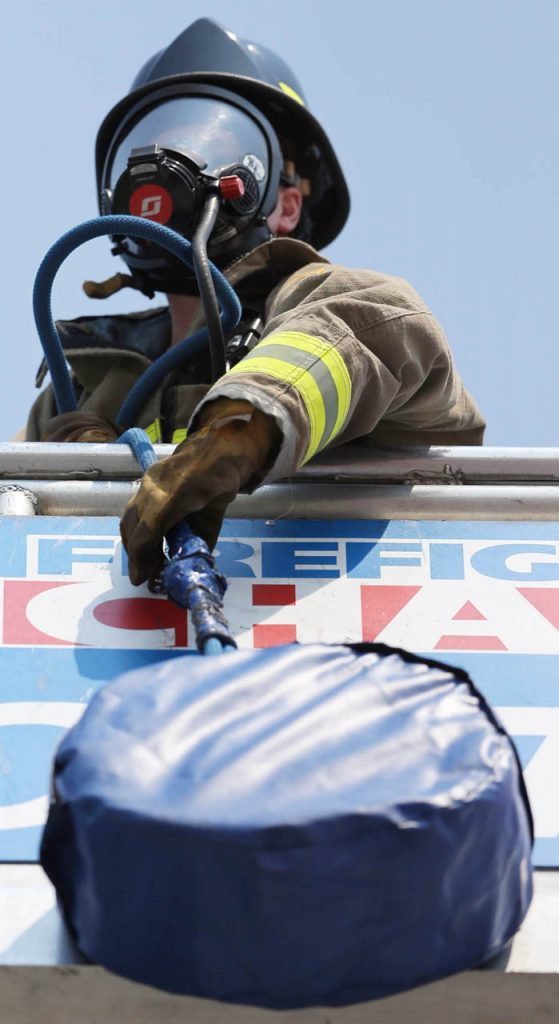 Tricia Faimon, a volunteer firefighter with the Hadar, Neb. Fire Department, pulls a 42-pound donut up a 40-ft. stair tower during the Scott Firefighter Combat Challenge Saturday at the Nebraska State Fair. Faimon was the only female firefighter in the competition.