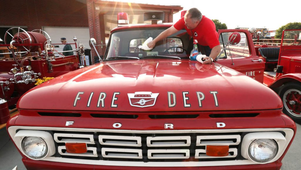 Joel Cerny, fire chief of the Linwood Rural Fire Protection District, cleans the windshield of a 1964 Ford 4x4 grass rig at the Nebraska State Fair.