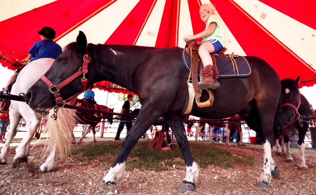 Josie Eichholz of Pleasanton, Neb. rides a pony named Pedro as she and other children go on a pony ride Saturday at the Nebraska State Fair.