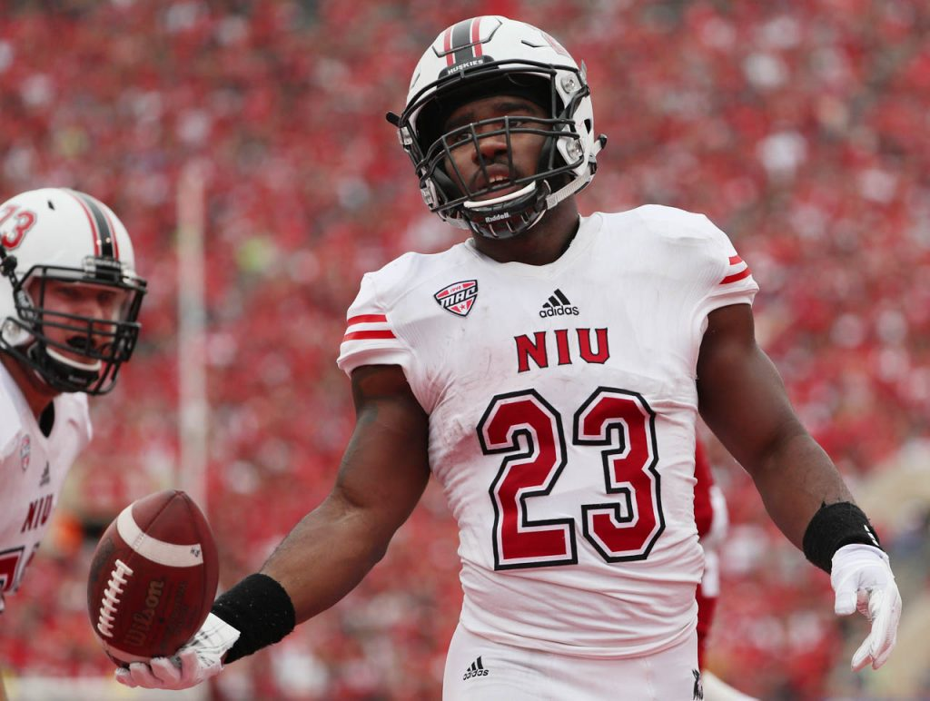 Northern Illinois tailback Jordan Huff tosses the football to a referee after scoring a touchdown against Nebraska.