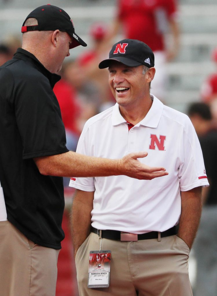Head football coaches Rod Carey of Northern Illinois, left, talks with Mike Riley of Nebraska prior to kickoff.