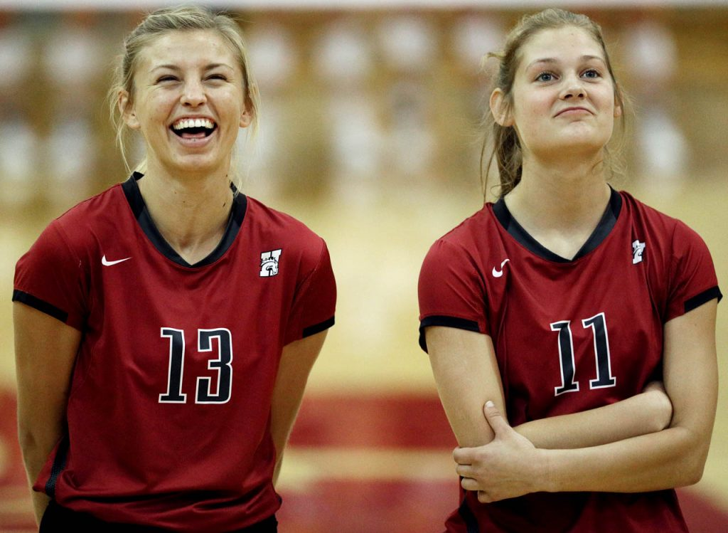 Hastings College sophomore Cassidy Ostrand (13) and freshman Elise Baumann watch highlights on a videoboard prior to opening introductions of players.