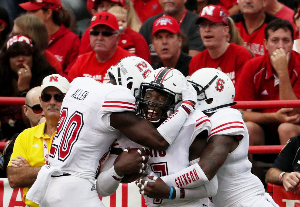 Northern Illinois teammates Mycial Allen (20) Jawuan Johnson (7) and Bobby Jones IV celebrate Johnson's pick six touchdown against Nebraska.