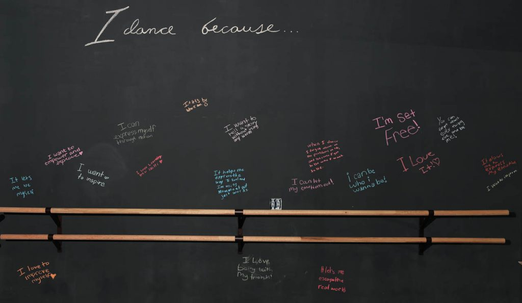 Dancers wrote with chalk on a blackboard why they like dancing.