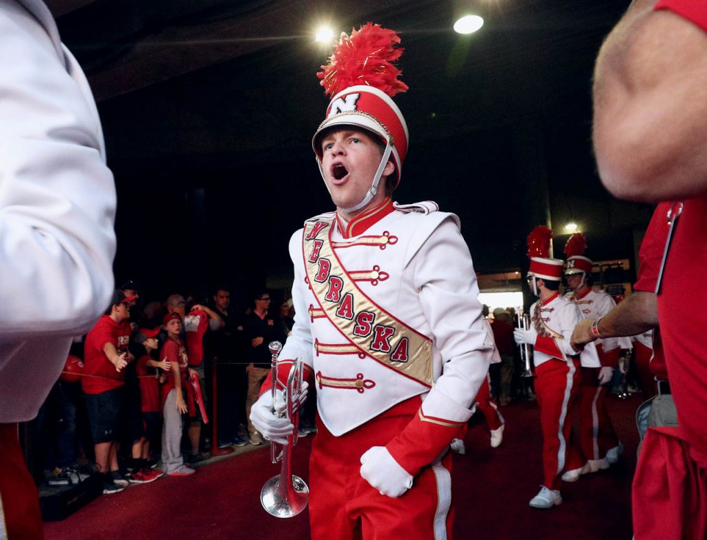 A member of the Nebraska Cornhuskers Marching Band yells out while coming out of the tunnel at Memorial Stadium.