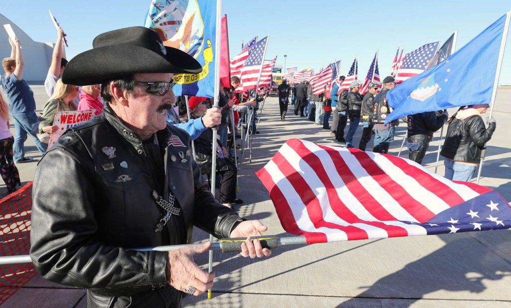 Patriot Guard Rider Tom Whalen of Greeley unravels an American flag during a Hero Flight Welcome Home Wednesday at the Central Nebraska Regional Airport.
