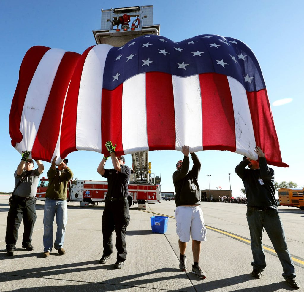Grand Island Fire Dept. station one Cpt. Tom Cox, Brandon Stahl, maintenance technician with Hall County Airport Authority, firefighter Chad Michel, Dylan Evans, maintenance technician and Wesley Harris, a maintenance supervisor slowly unravel an American flag as Leslie Harmon raises the ladder on a fire engine during a Hero Flight Welcome Home Wednesday at the Central Nebraska Regional Airport.