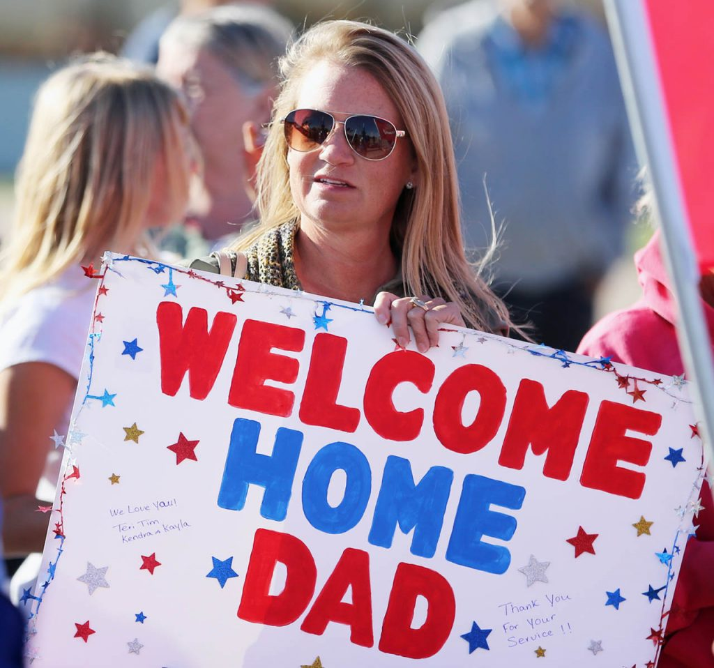 "Teri Micek of Marion, Iowa holds a sign that says ""welcome home dad"" during a Hero Flight Welcome Home Wednesday at the Central Nebraska Regional Airport. Micek's father Jim Thompson is a Vietnam Navy veteran."