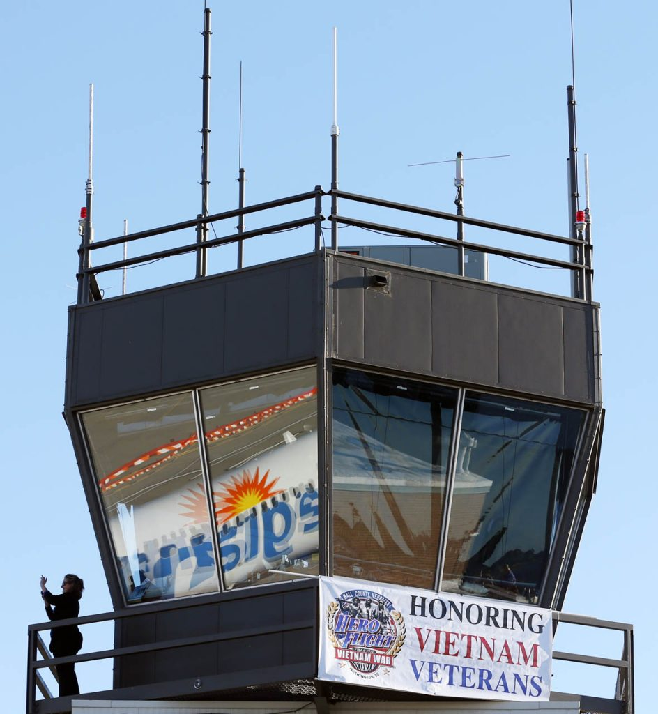 An individual takes pictures from the Central Nebraska Regional Airport tower as an Allegiant flight arrives during a Hero Flight Welcome Home Wednesday.