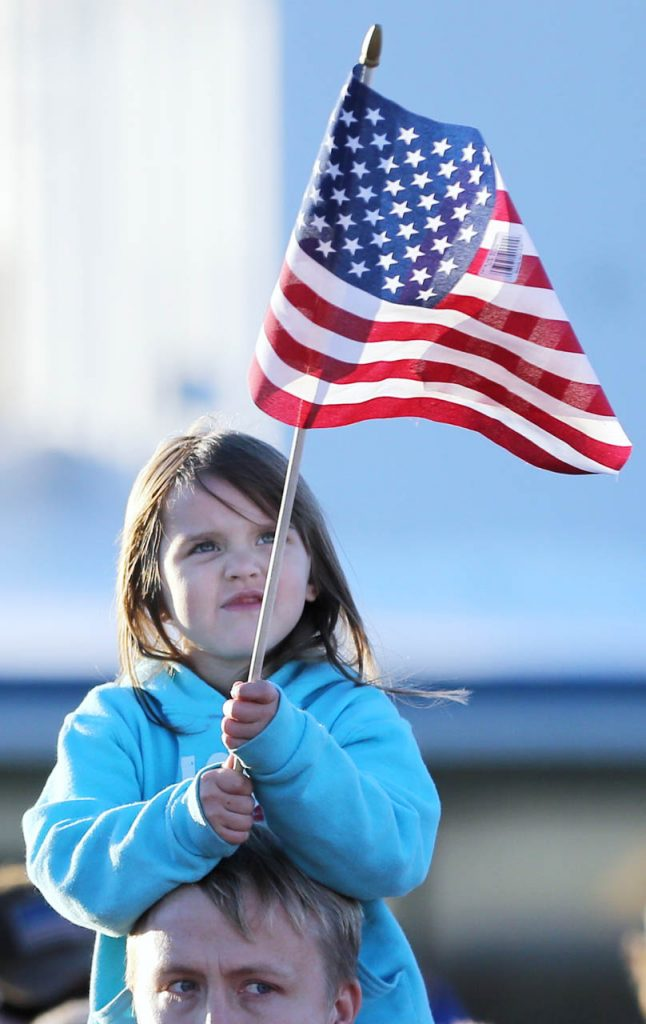 Jesse Gay holds his daughter Abby on his shoulders as she holds an American flag during a Hero Flight Welcome Home Wednesday.