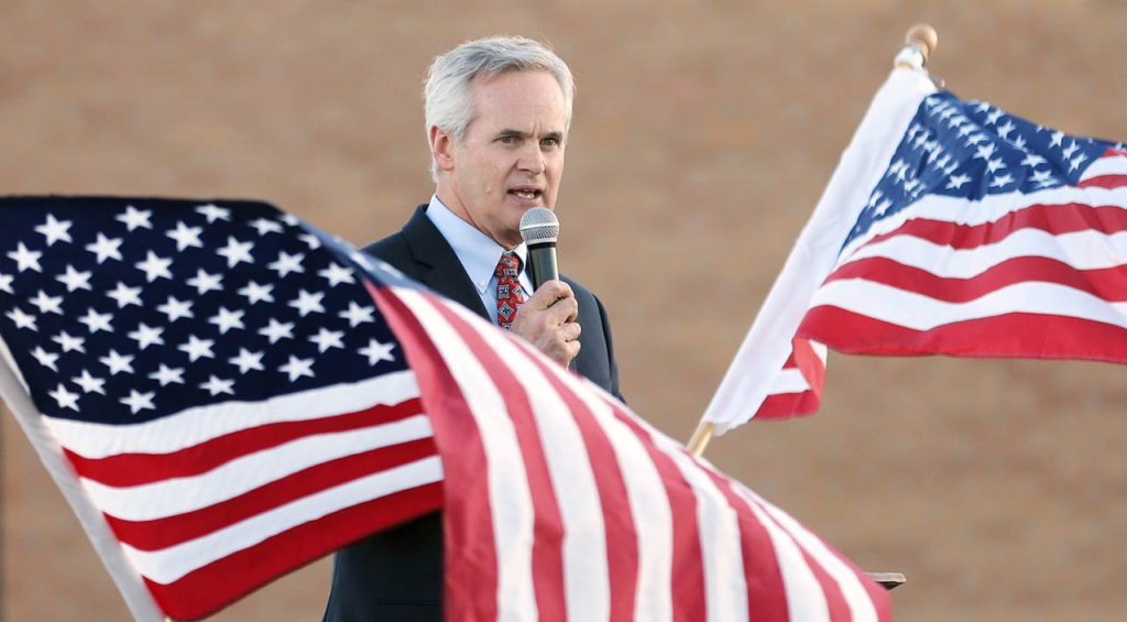 American flags wave around Nebraska Lt. Governor Mike Foley during a Hero Flight Welcome Home Wednesday at Central Nebraska Regional Airport.