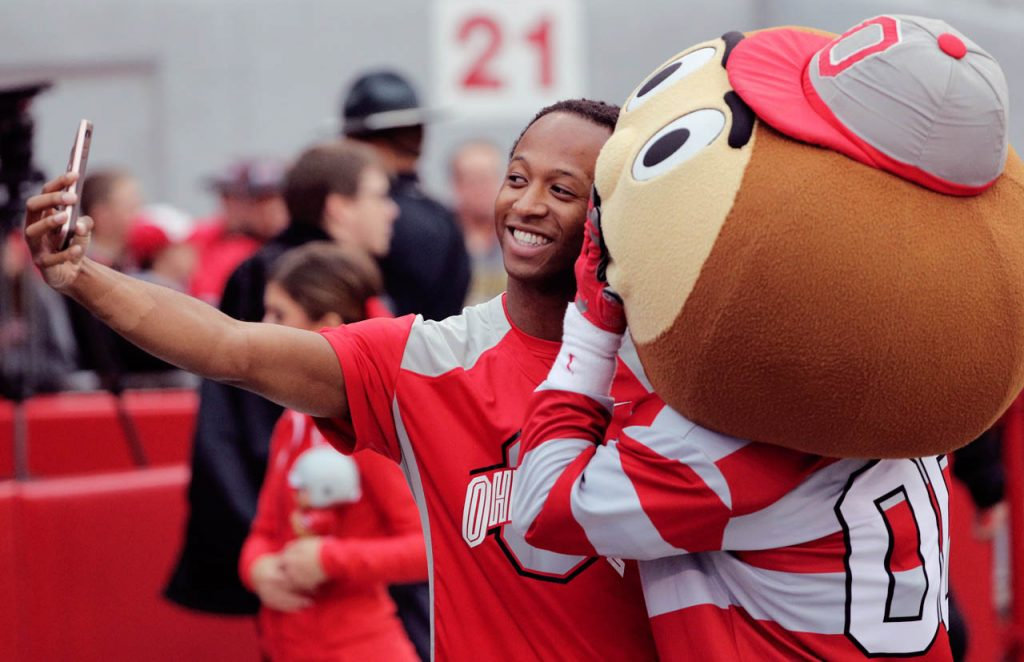 An Ohio State cheerleader takes a selfie with Buckeye the mascot.