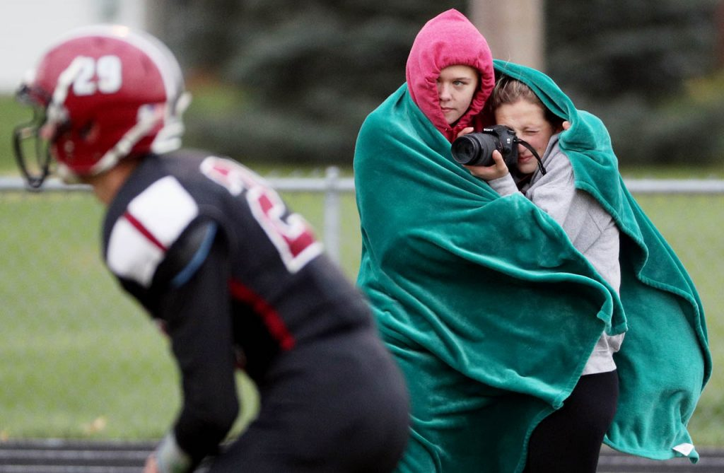 Johnson-Brock student Logan Edwards shares her blanket to shield her classmate Hailee Sandfort from the cold wind as she takes photos of an 8-man playoff football game against Heartland Thursday in Henderson.