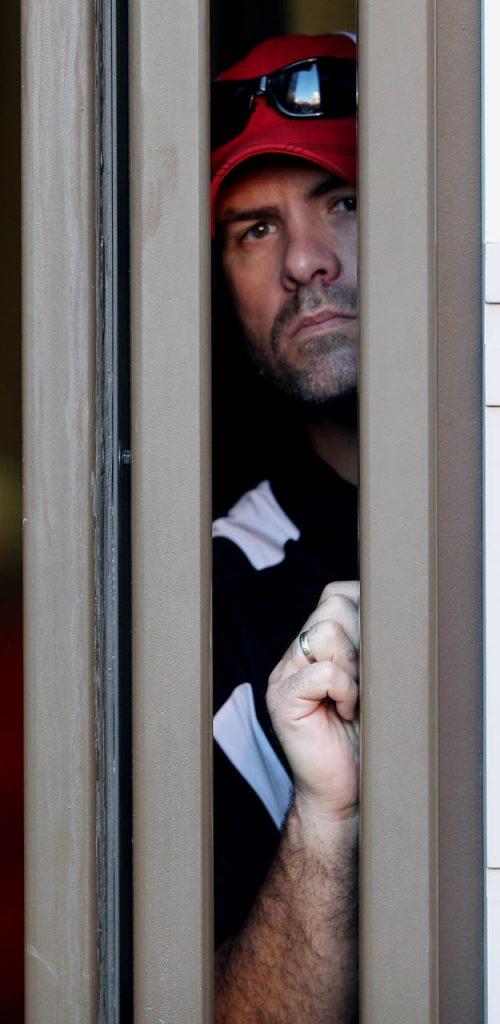 A Huskers fan peers out between an opening between retractable doors at Memorial Stadium.