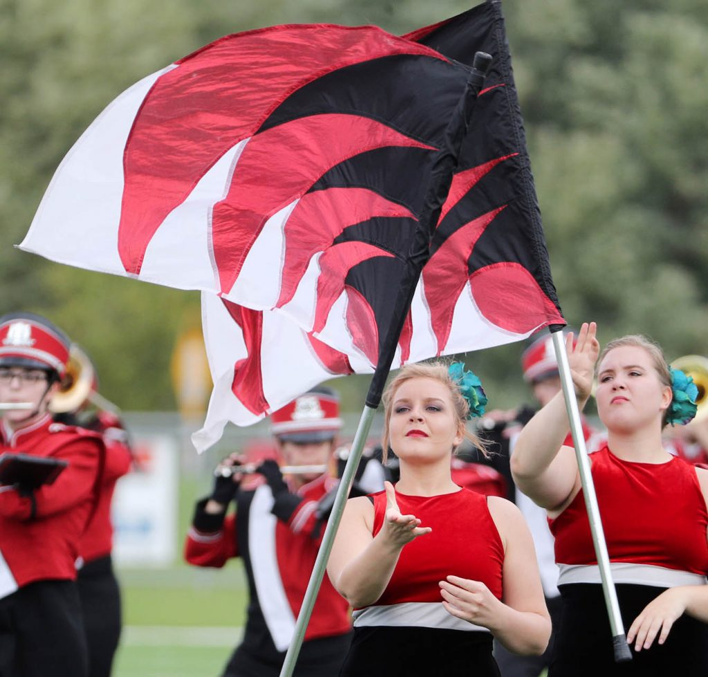 Members of the Hastings College Marching Band twirl flags while performing prior to kickoff.