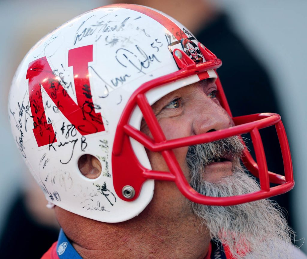 A Huskers fan wearing an autographed football helmet arrives for the game.