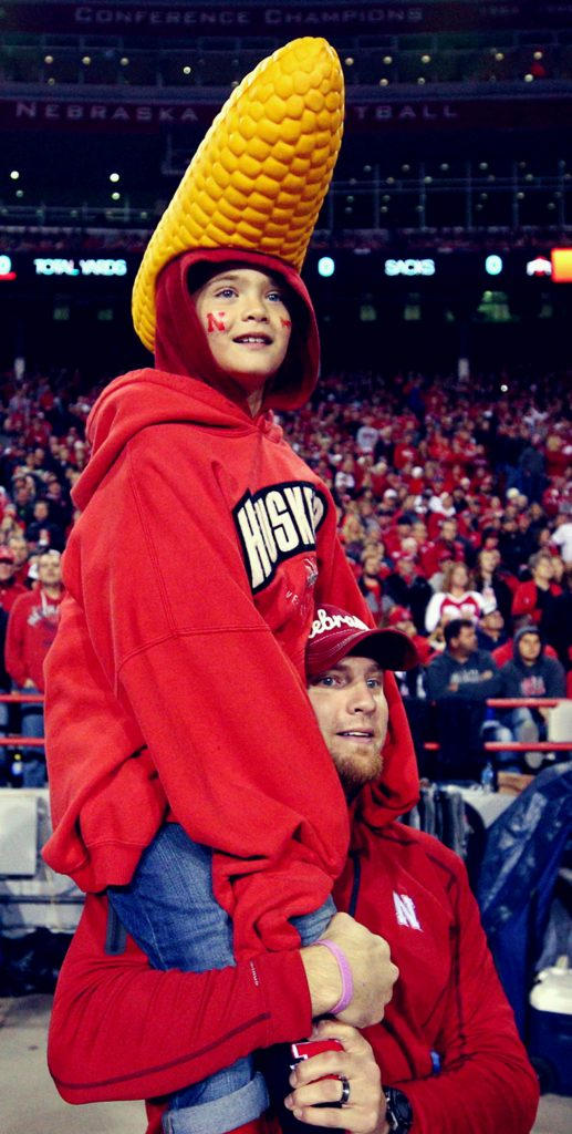 Bob DeBusk of Atlanta, Ga. holds his son Luke on his shoulders for a view over the Ohio State team bench Saturday night at Memorial Stadium. DeBusk is originally from Alliance. (Independent/Andrew Carpenean)