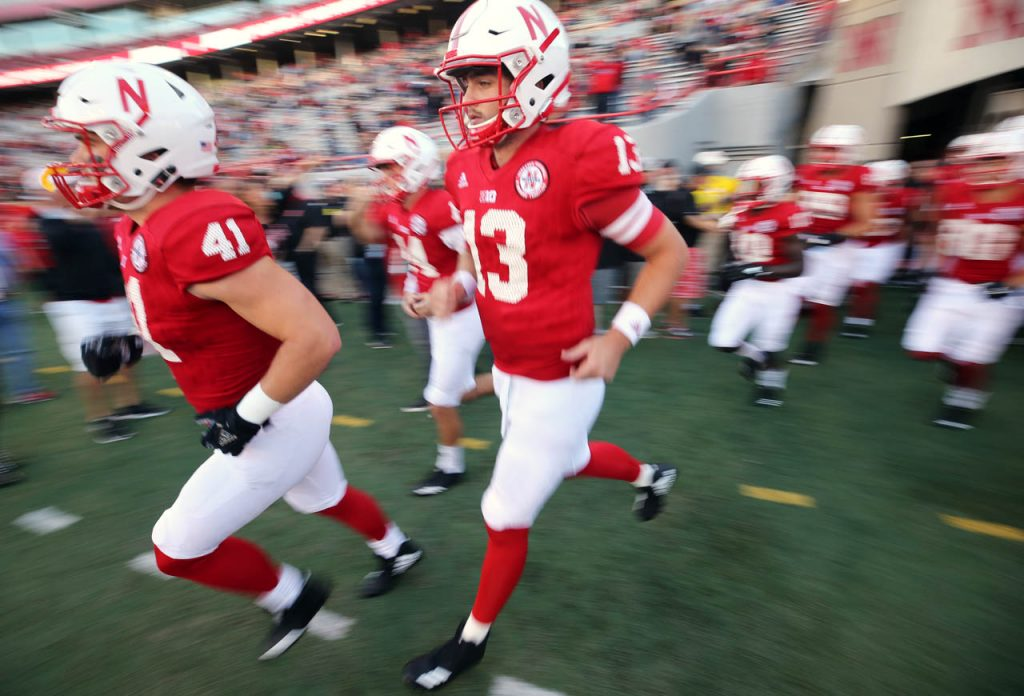 Nebraska junior quarterback Tanner Lee runs onto the field with his teammates to warm up against Wisconsin at Memorial Stadium.