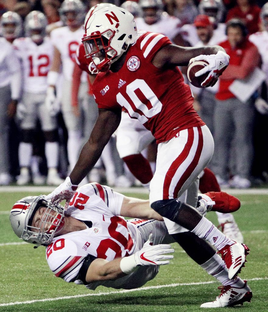 Nebraska wide receiver JD Spielman stiff arms Ohio State linebacker Pete Werner on a kickoff return Saturday night at Memorial Stadium. (Independent/Andrew Carpenean)